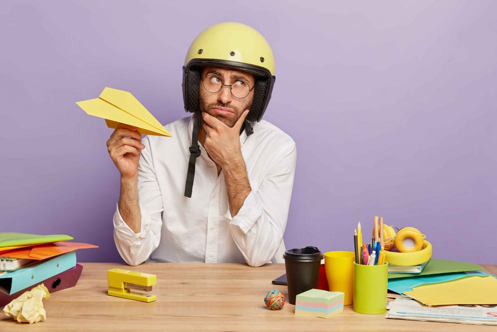 pensive-thoughtful-young-man-tired-working-office-holds-paper-handmade-plane-wears-protective-helmet-white-shirt-holds-chin-thinks-about-changing-job-position